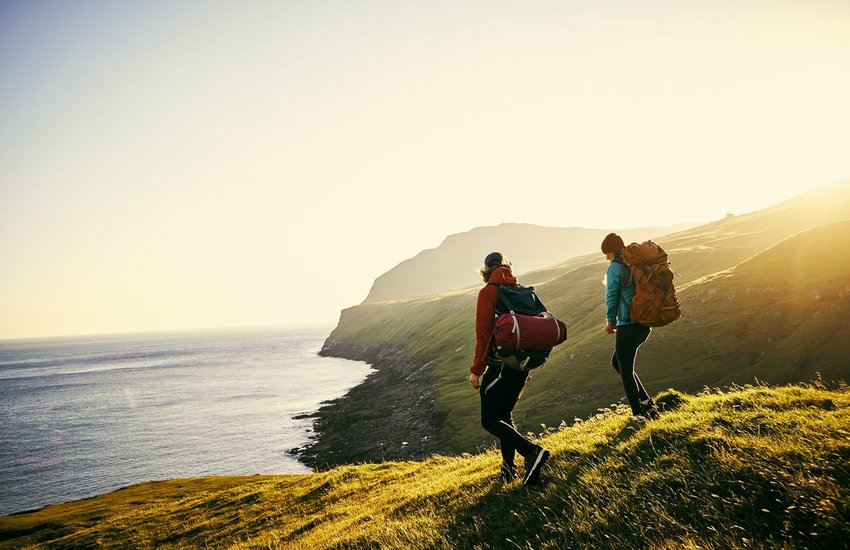 Two people backpacking on green hills overlooking the ocean