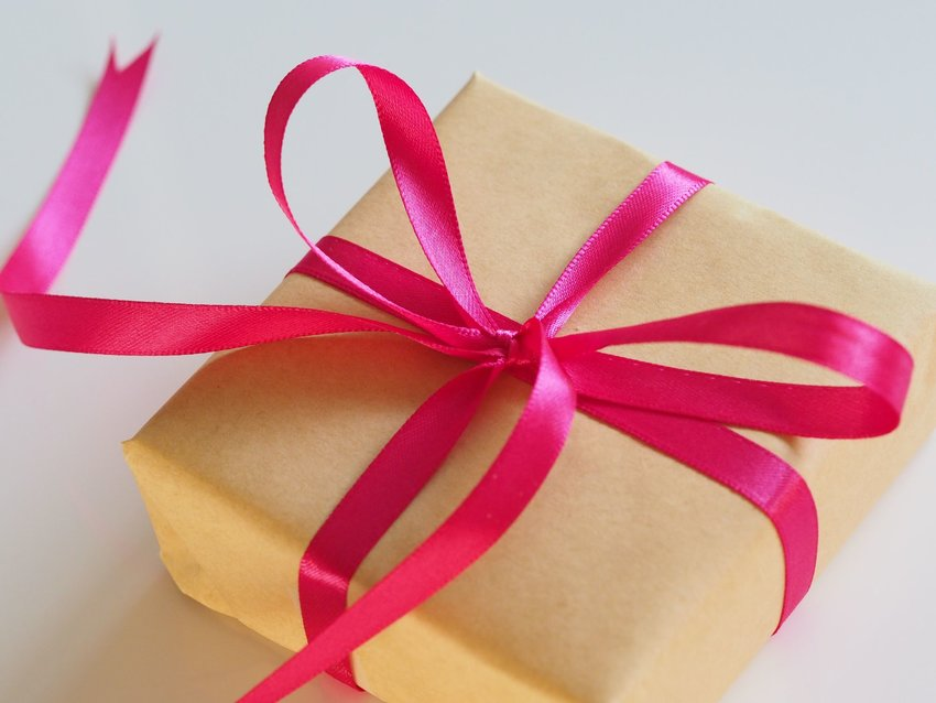 Brown paper wrapped box with a pink ribbon tied into a bow
