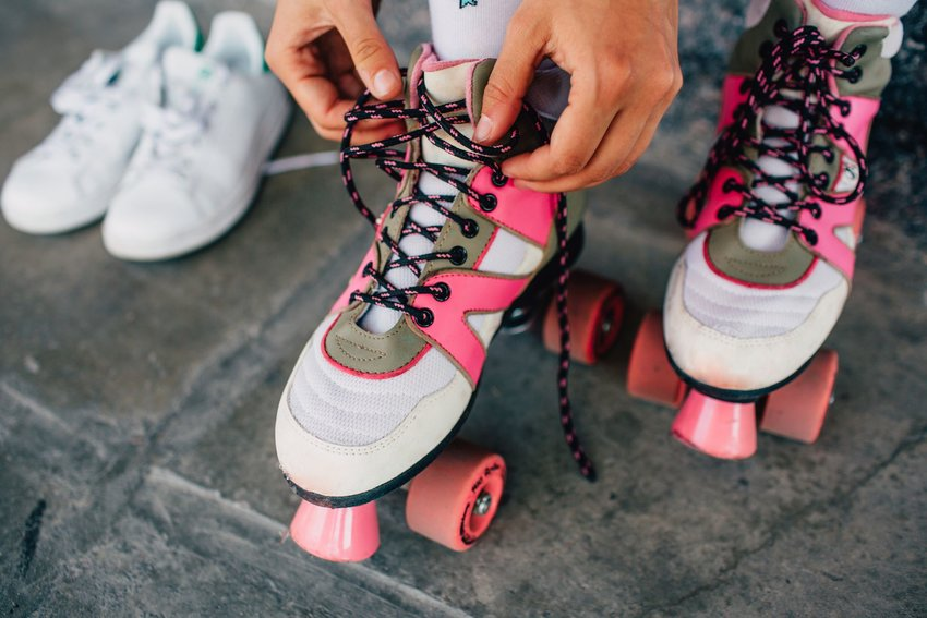 Person lacing up pink roller skates