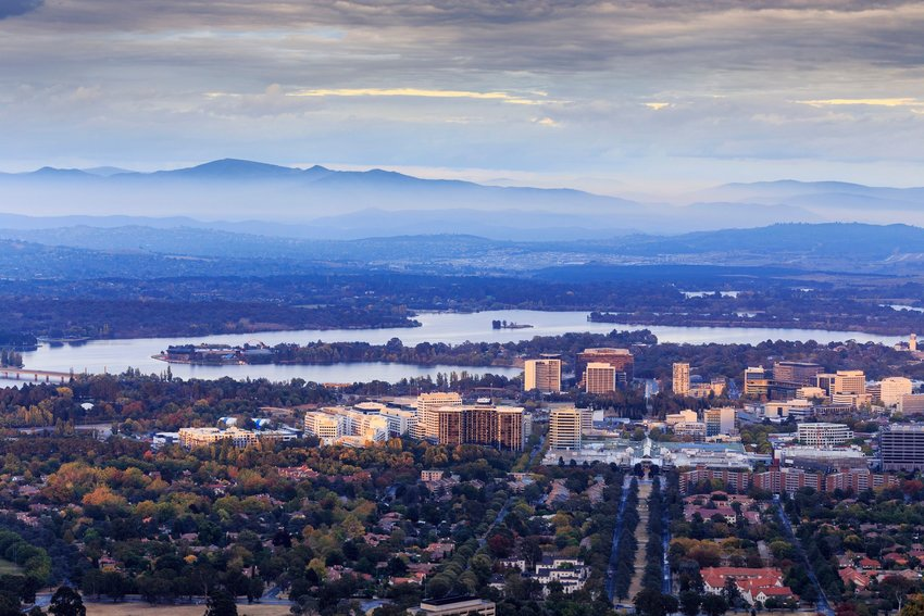 A view of downtown Canberra and a river with mountains rising out of the morning mist