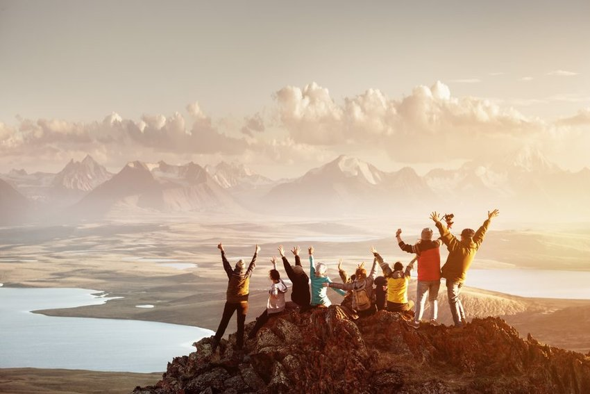 Group of people celebrating on top of mountain with mountain range in the background