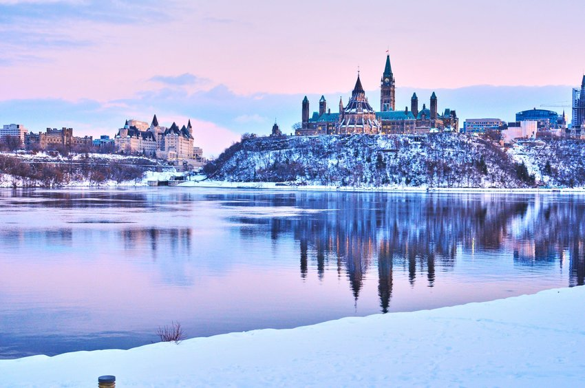 A beautiful blue and purple sunset with the snow-covered castle-like Canadian Parliament building.