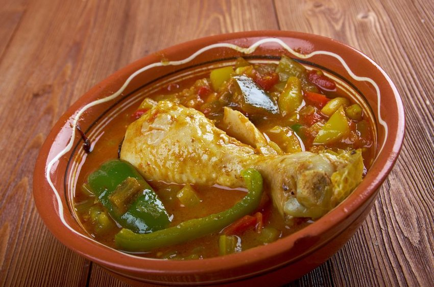 Chicken muamba in a red bowl with peppers and okra