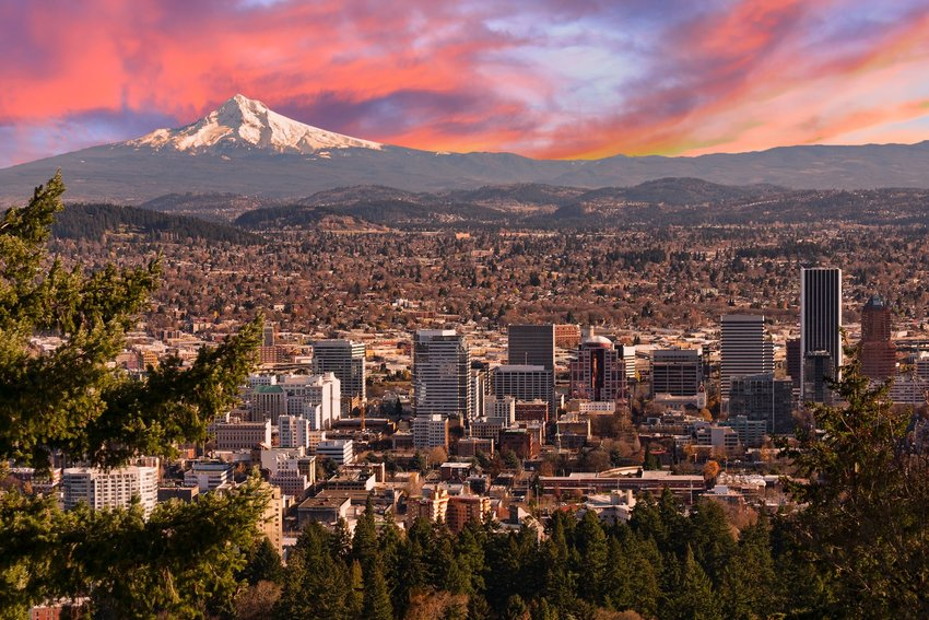Downtown Portland, Oregon with Mount Hood in the background against a pink and purple sunrise