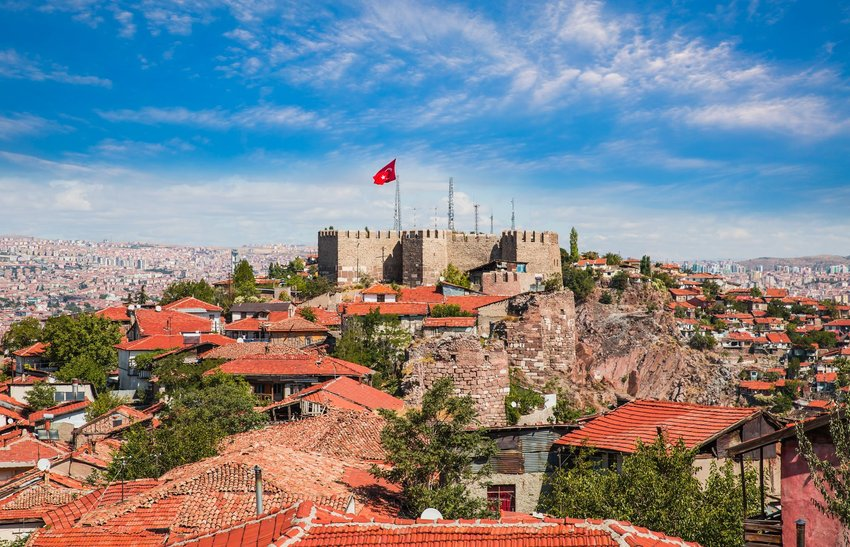 Ankara castle with a red flag stands on a hill with the surrounded red-roofed buildings