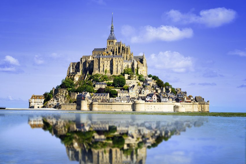 Mont Saint-Michel with green trees and a blue sky reflected in the water during high-tide