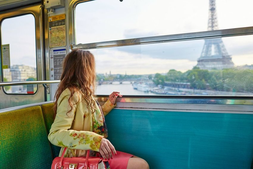 Person on train through Paris with window view of the Eiffel Tower