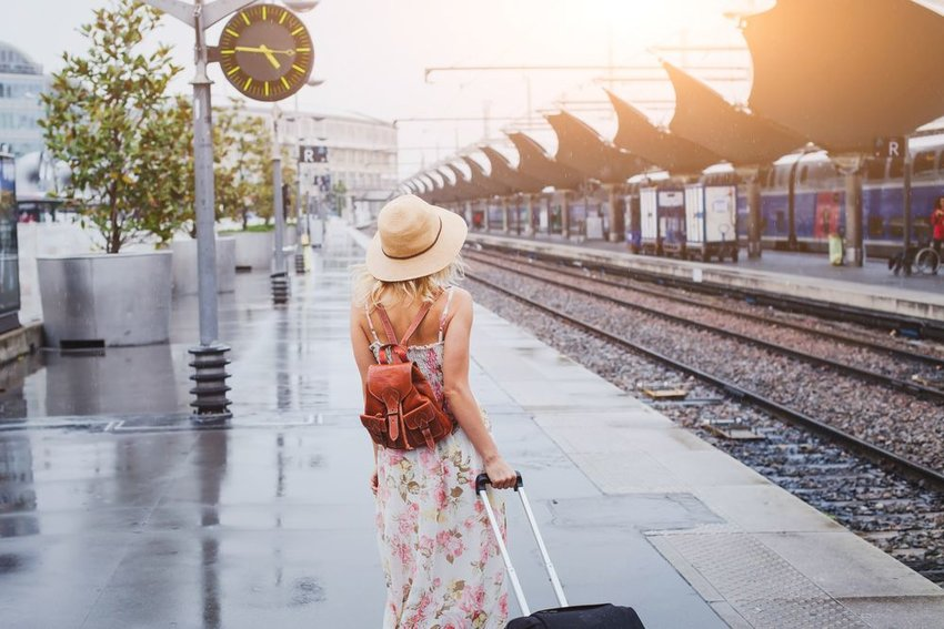 Woman traveling alone with suitcase at train station