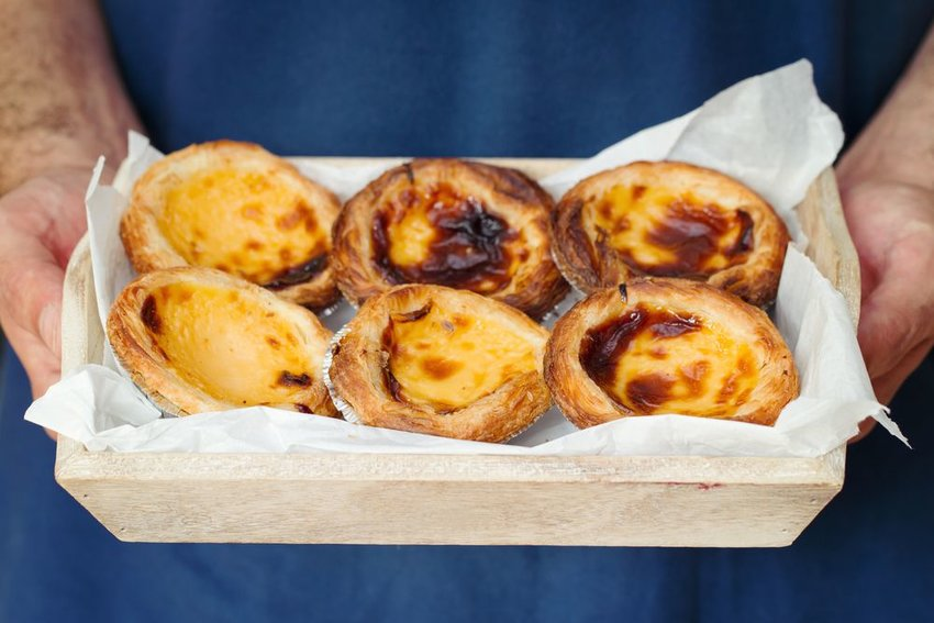 Pasteis de Nata held in a wooden tray