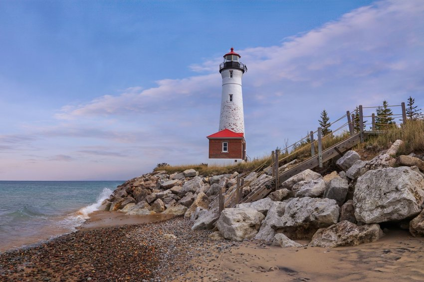 A white and red historic lighthouse on the shore of Lake Superior in Michigan's Upper Peninsula.