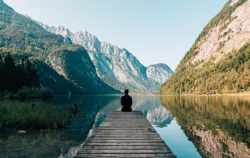 Person sitting at the end of a dock over a lake with mountains in the distance