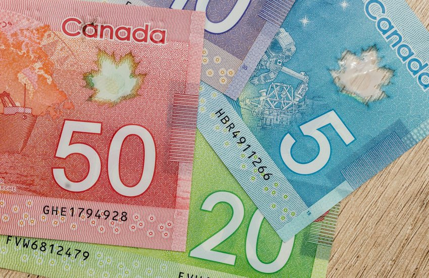 Canadian banknotes with bright colors on a wooden table