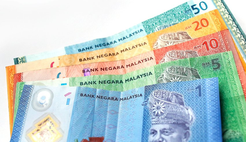 Malaysian banknotes with different denominations spread out across a white background