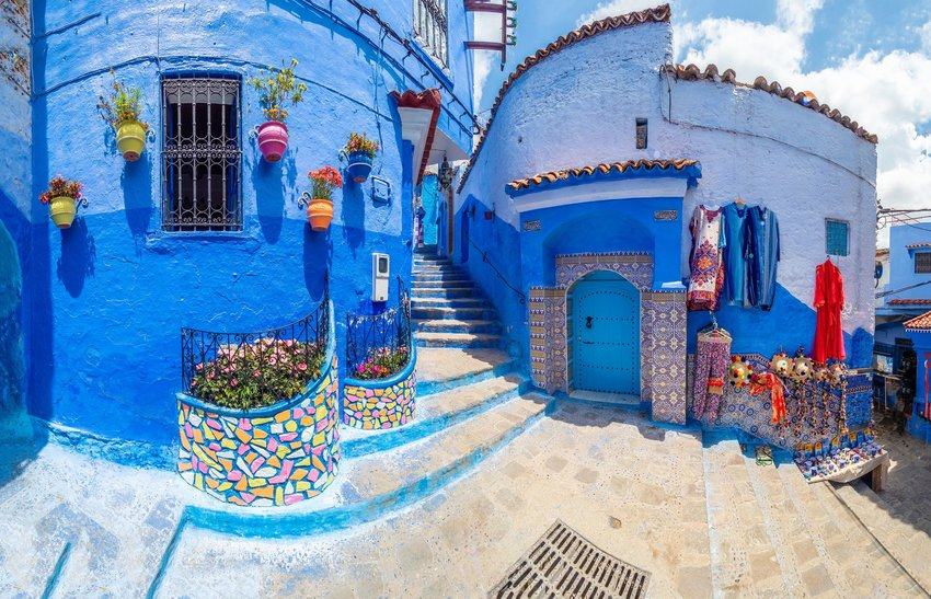 Chefchaouen alleyway with blue walls, textiles, and flowers