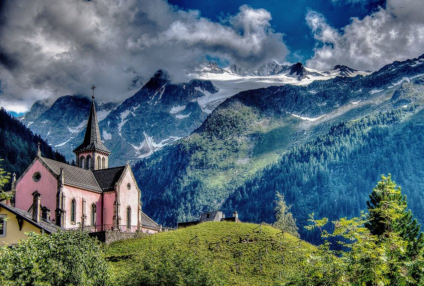 Pink church with low clouds and alpine mountains in the background