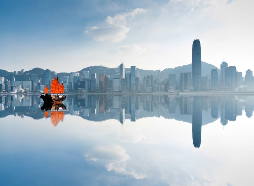 Hong Kong skyline reflected in the water with a brightly colored boat