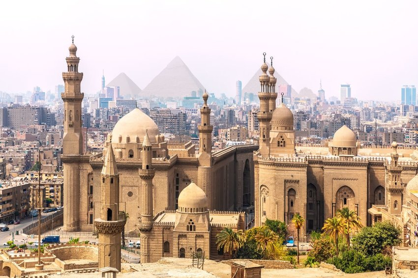 A mosque in the city of Cairo, Egypt, with the pyramids of Giza in the background
