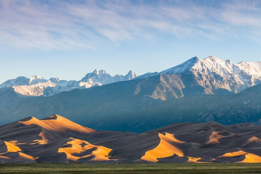 The golden sand of the Great Sand Dunes with snow-topped mountains in the background in southern Colorado.