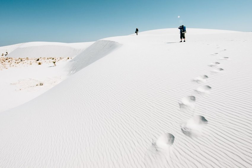 Two people walking on white dunes on clear, blue day