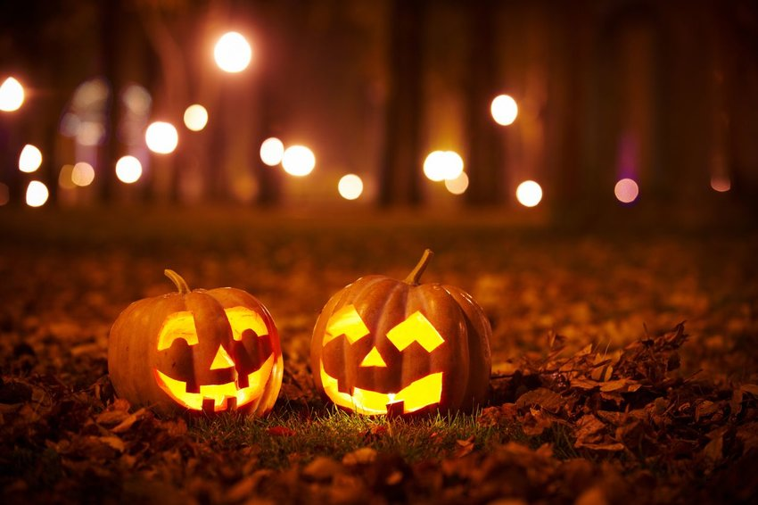 Two jack-o-lanterns sitting in leaves
