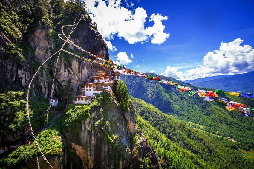 The Tiger Monastery in Bhutan, built into the side of a mountain with prayer flags