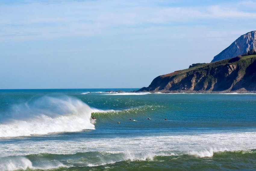 Surfers and waves in Mundaka, Spain