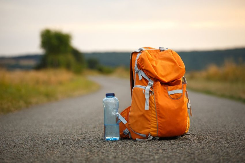 Orange backpack with water bottle sitting on road