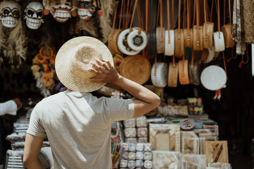 Young man in a straw hat stands in front of a local souvenir booth with bags and local goods in Bali.