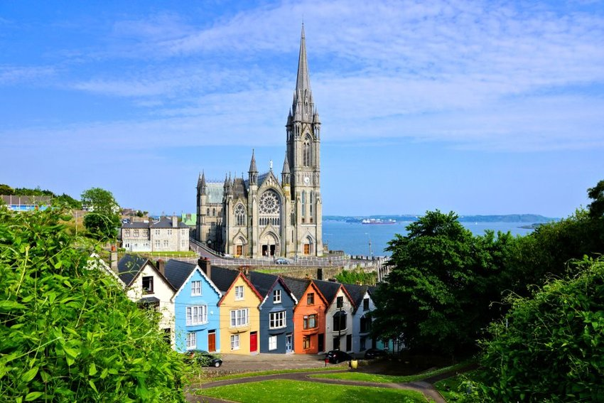 Colorful row houses with towering cathedral in background