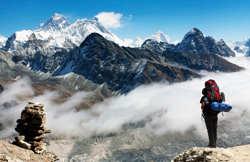 A backpacker looks toward the snowy peak of Mount Everest