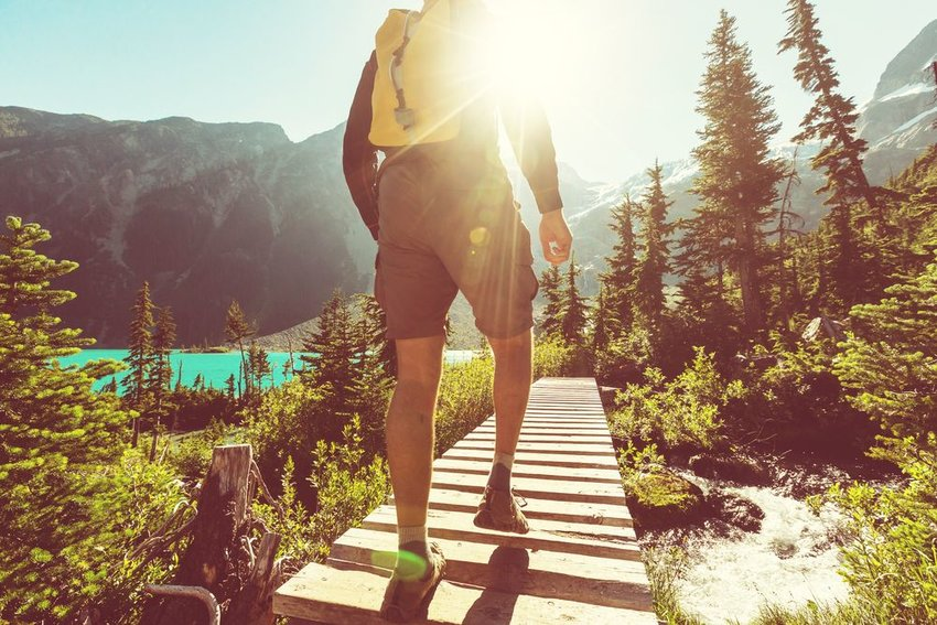 Person walking along a man made walkway with mountains in the background
