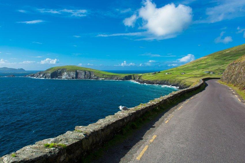 Coastal road running along the ocean and beneath a blue sky