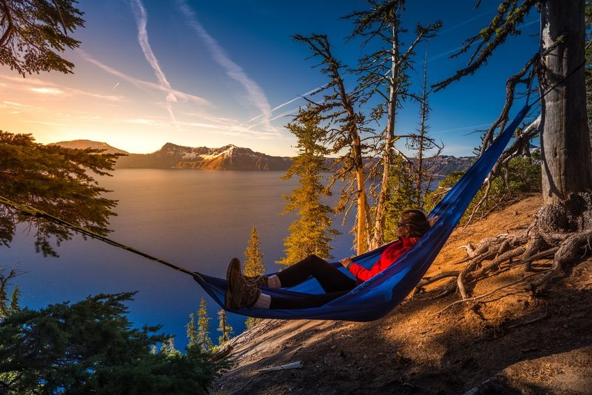 Person relaxing in hammockwith view of mountain and lake