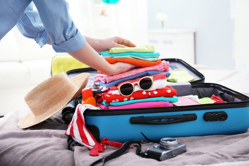 A woman packing a suitcase with a variety of items she may need on a trip