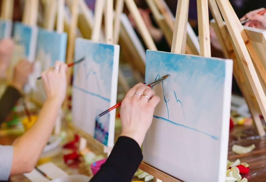 Row of people painting on canvases