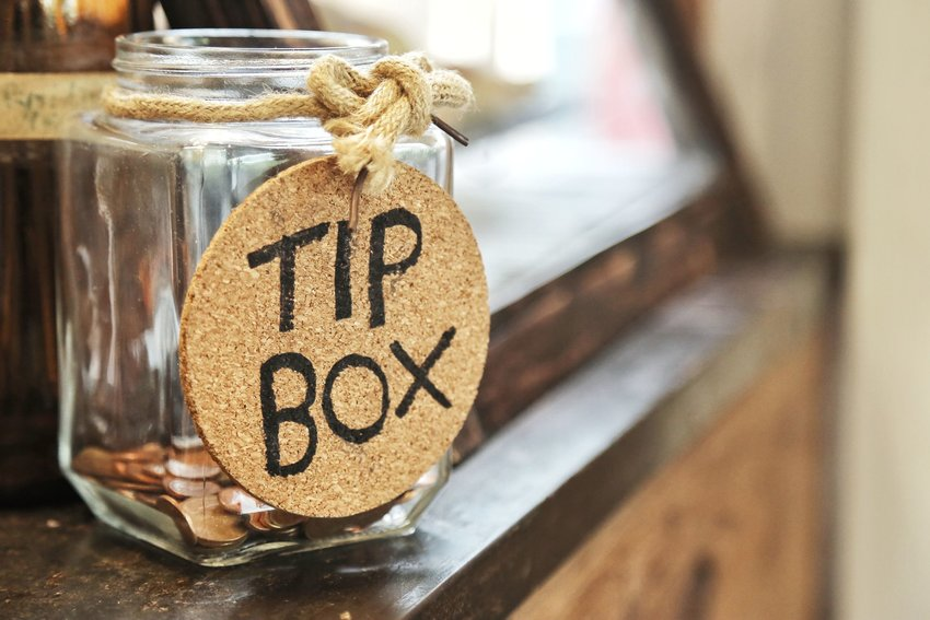 "Glass jar with coins and a cork ""Tip Box"" sign tied around the neck with rope"