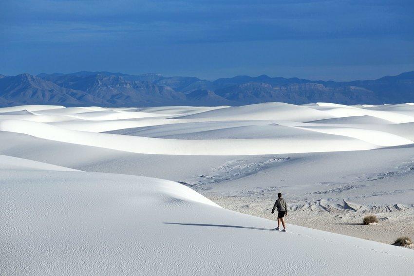 Man walking across dunes at White Sands