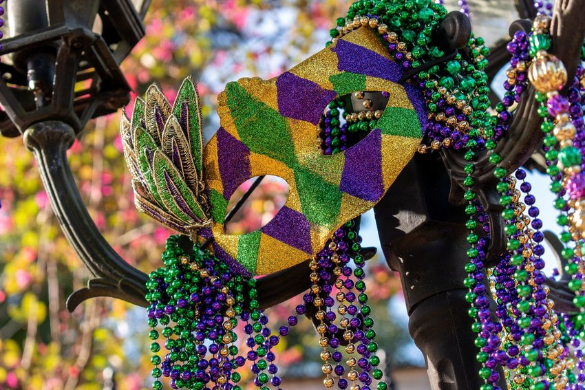 Green, gold, and purple Mardi Gras mask hanging on a street lamp