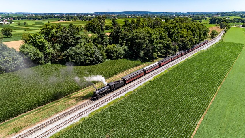 Train in the countryside next to green fields and trees in Pennsylvania