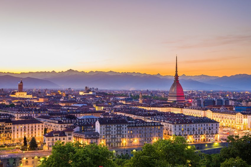 Cityscape of Torino (Turin, Italy) at sunset with lit streets