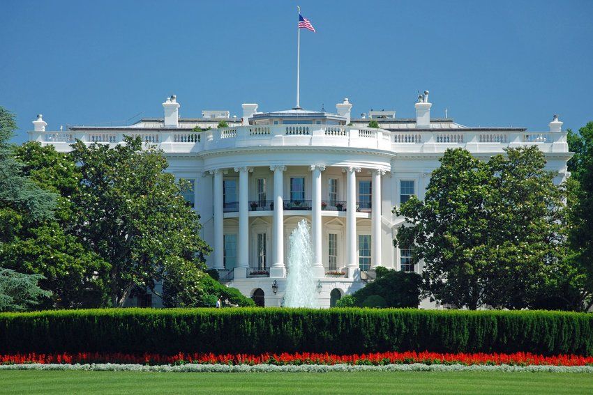 The front of the White House against a clear blue sky