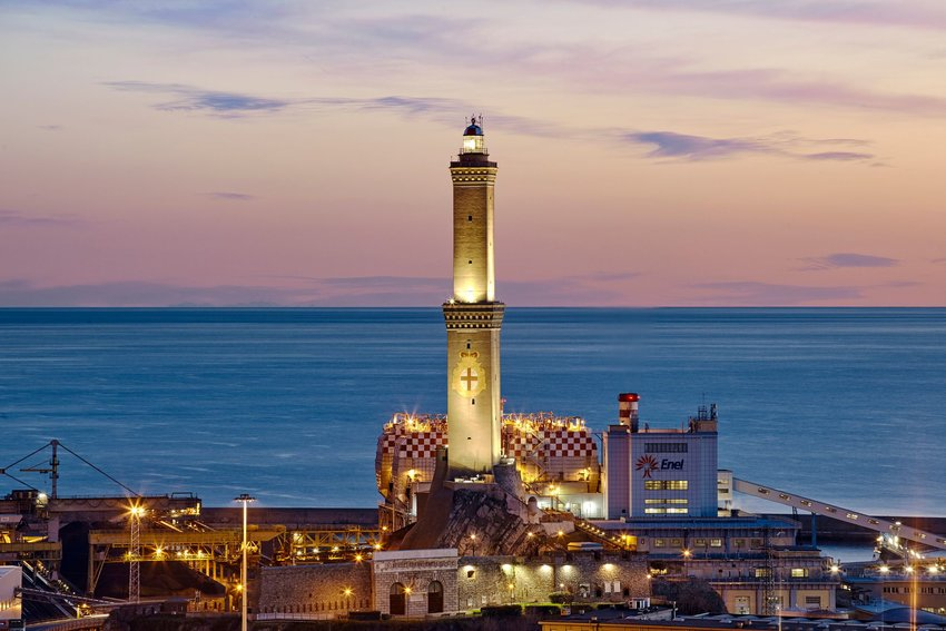 Lighthouse, sea, and buildings in Genoa at sunrise