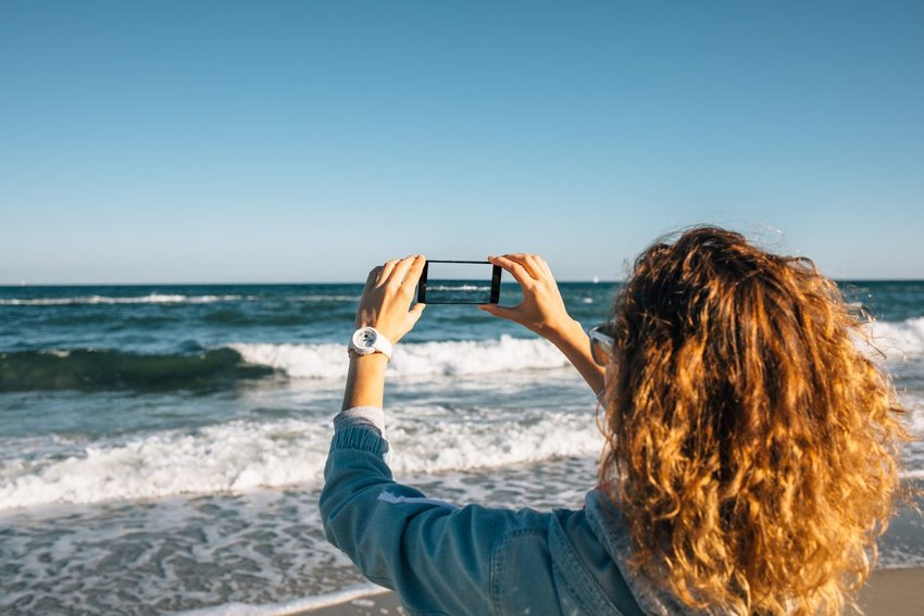 Person taking photo with phone of the ocean