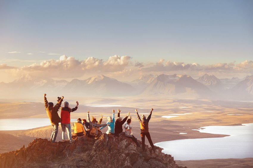 Group of people throwing hands in the air at top of mountain