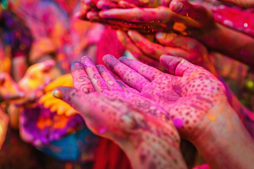 Hands covered in bright colors at Holi