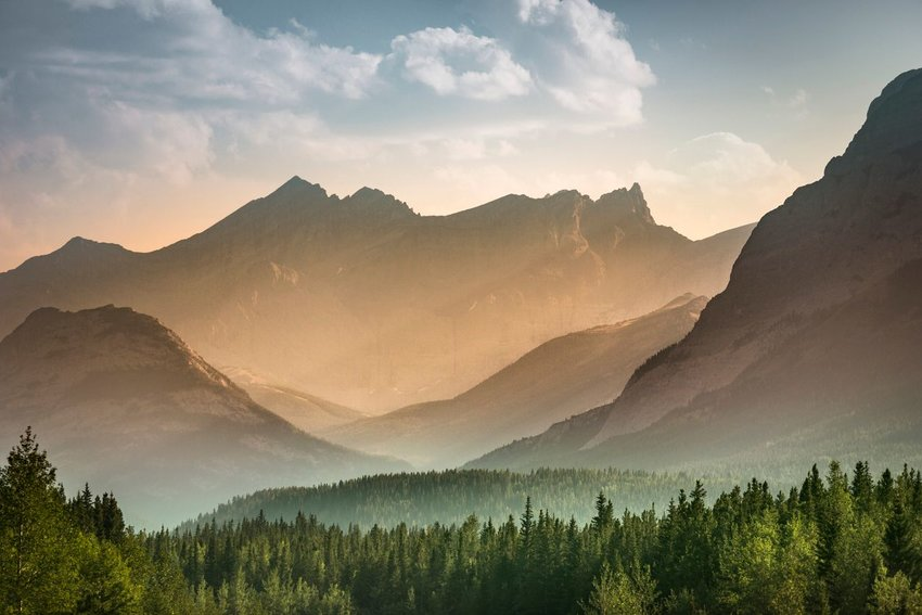 Sun streaking through mountains with green forest below