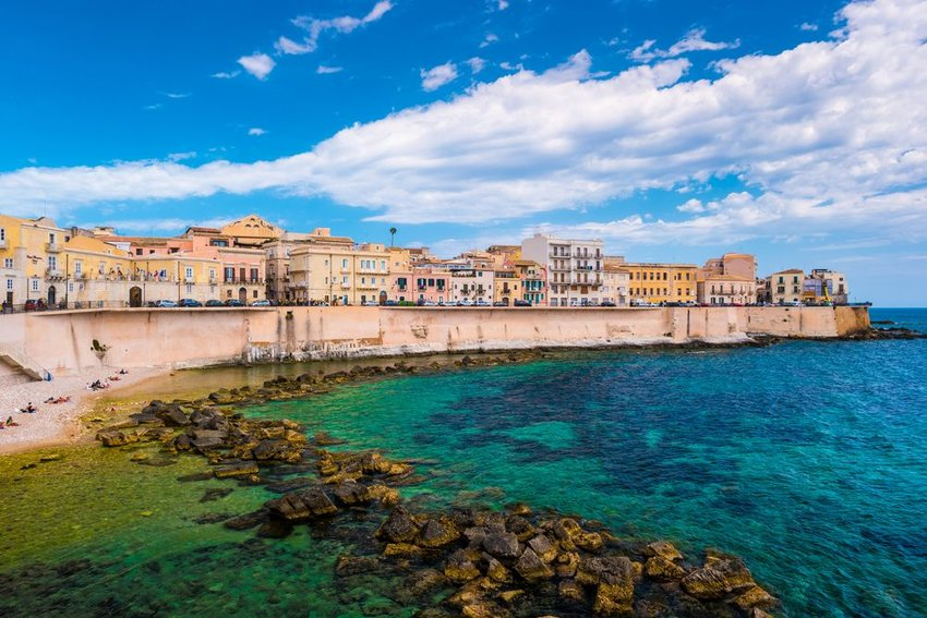 Buildings on the water in Syracuse, Sicily with blue water in front