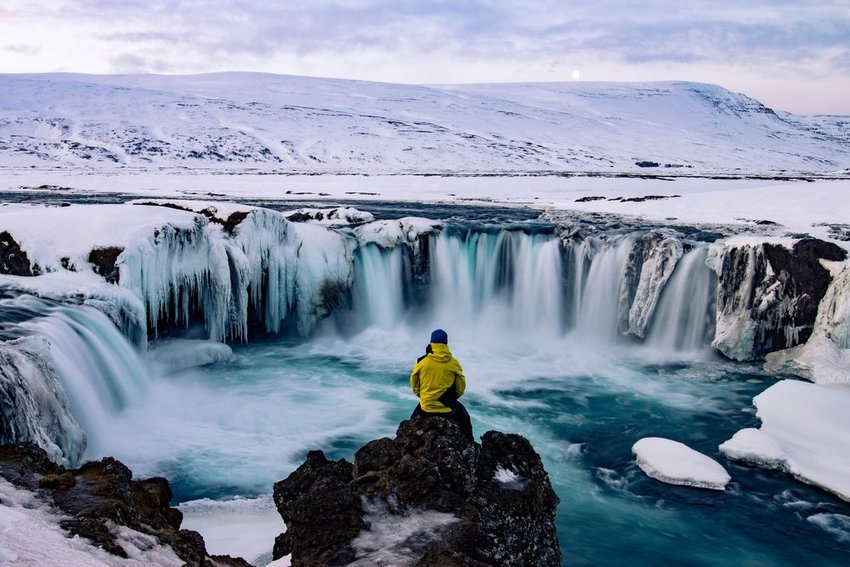 Person sitting alone in front of icy waterfall