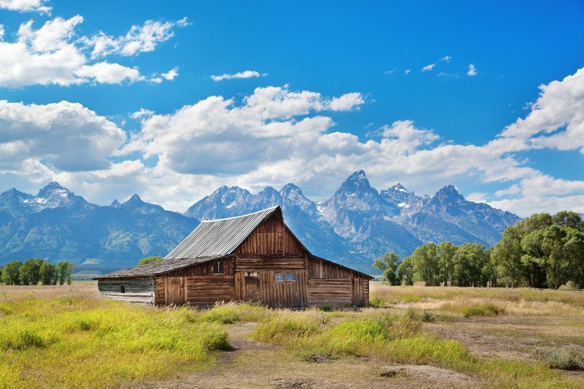 An old farmhouse in Grand Teton National Park with the Teton Range in the background