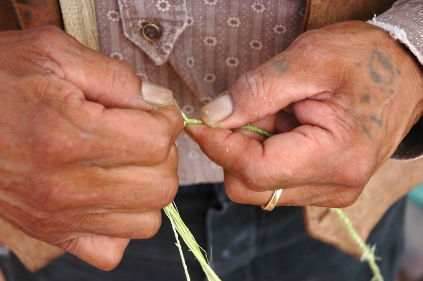Man making yucca cord with hands that have a skin stitch tattoo